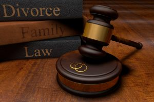 Gavel, divorce law books and wedding rings