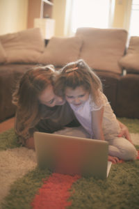 Mother and daughter reading on laptop.