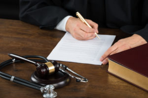 Judge Writing On Document With Mallet And Stethoscope At Desk